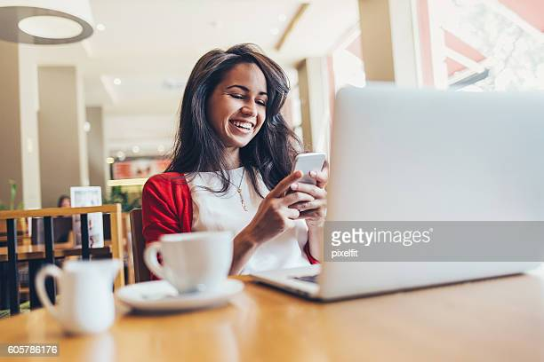 Girl with smart phone and laptop in cafe