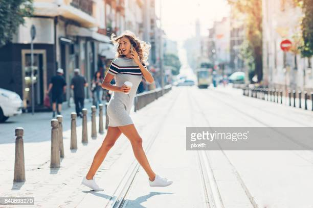 Girl with smart phone crossing the street