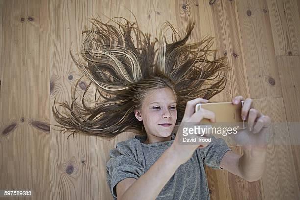 Girl with smart phone lying on a woodern floor.