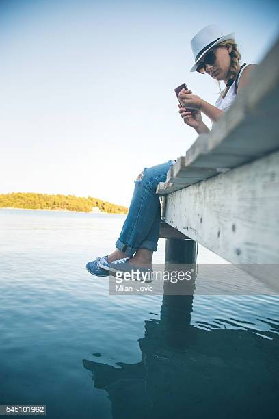 Girl with smartphone sitting at the pier
