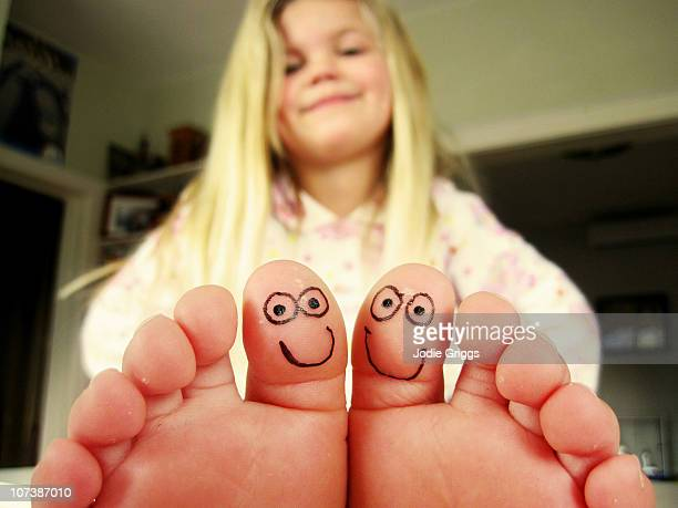 Girl with smiley faces drawn on toes