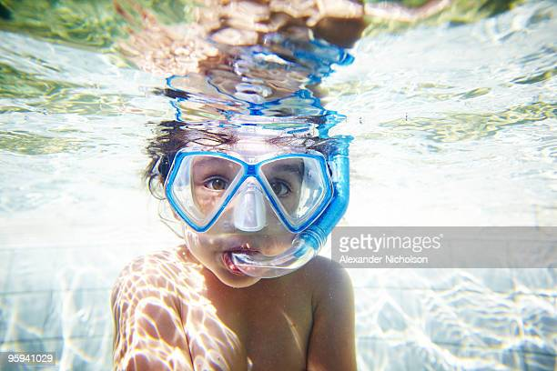 Girl with snorkel in pool, underwater view