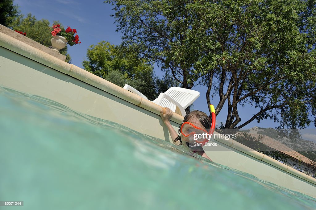 Girl with snorkeling gear in swimming pool : Stock Photo