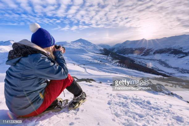 girl with snowshoes fotographs the landscape. livigno, valtellina, lombardy, italy, europe. - italia ストックフォトと画像
