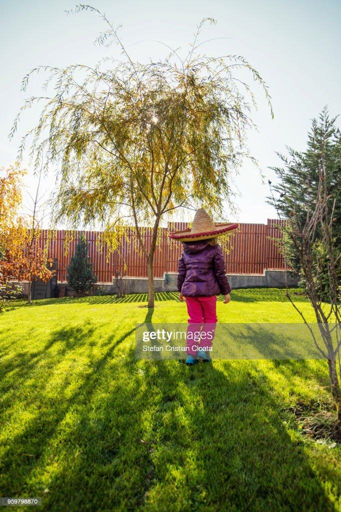 Girl with sombrero walking in backyard : Stock-Foto