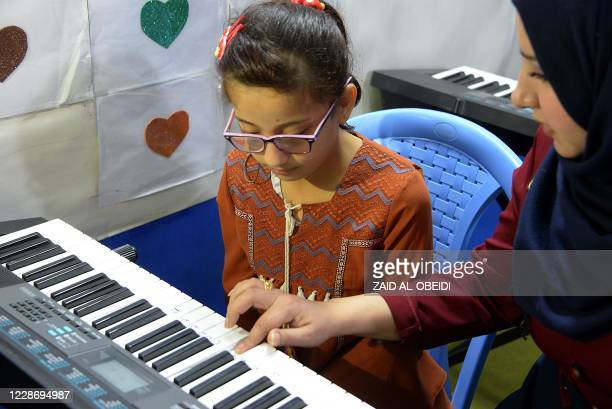 Girl with special needs practises a short eight-note tune to improve her motor skills at a rehabilitation centre in Iraq's northern city of Mosul on...