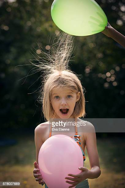 girl (7-8 years) with static hair and balloons - strom stock-fotos und bilder