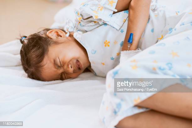 girl with stomachache lying on bed in hospital - appendix stock pictures, royalty-free photos & images
