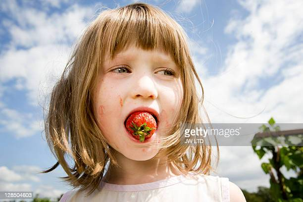Girl with strawberry in mouth, close up