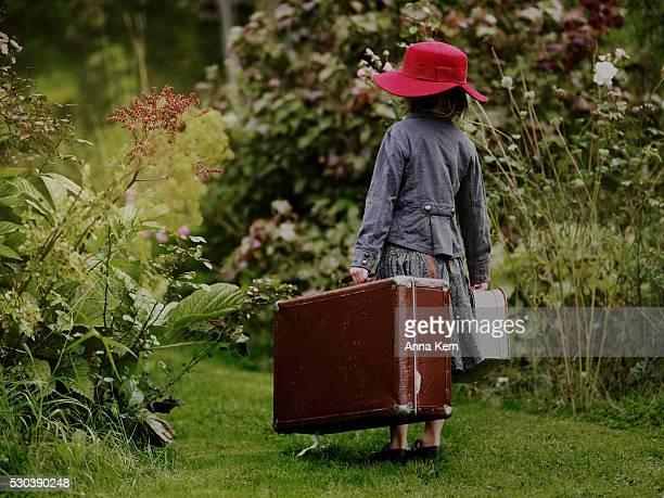 Girl with suitcases in garden, Varmdo, Uppland, Sweden