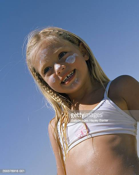 Girl (4-6) with sunblock on face, outdoors, low angle view, portrait