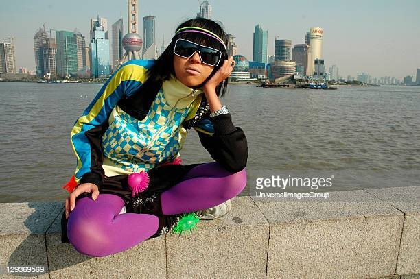Girl with sunglasses sitting on the bank of Huang Pu River, opposite the Oriental Pearl Tower. Shanghai, China 2007