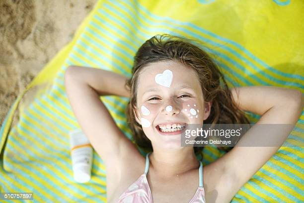 a girl with sunscreen on the face on the beach - girls sunbathing stock pictures, royalty-free photos & images