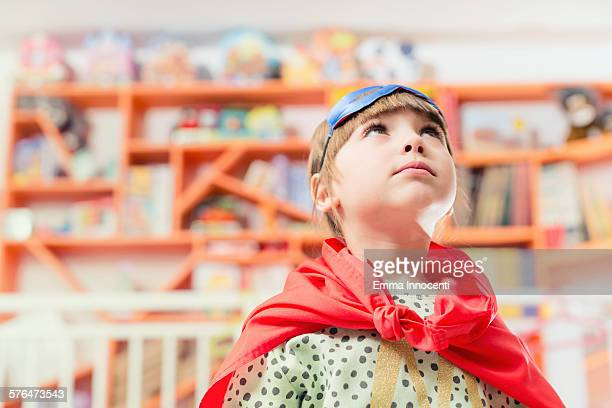 girl with super hero cape and mask looking up