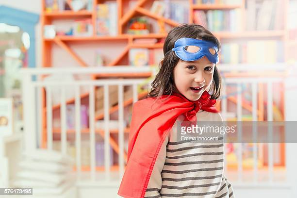girl with super hero mask and cape smiling