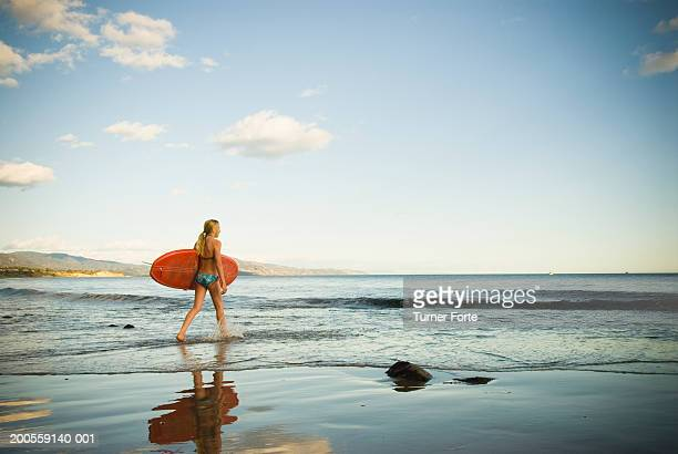 Girl (12-13) with surfboard on beach, side view