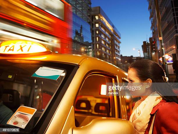 Girl with taxi in London by night