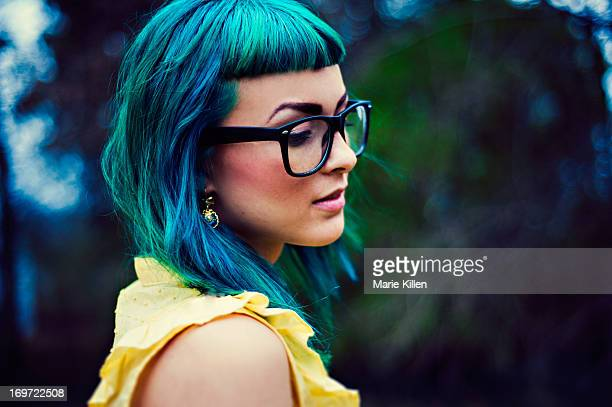 Girl with teal colored hair and glasses