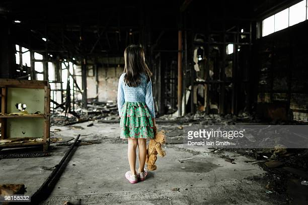 Girl with teddy bear in burned building