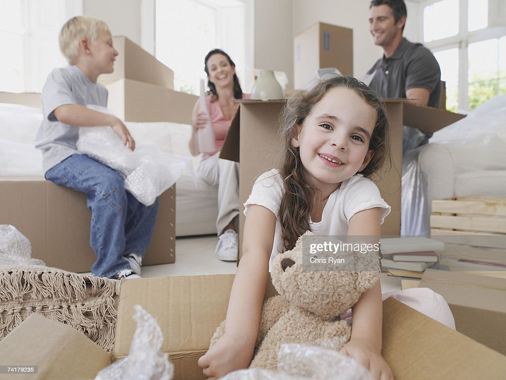 Girl with teddy bear in cardboard box with brother and parents in background : Stock Photo