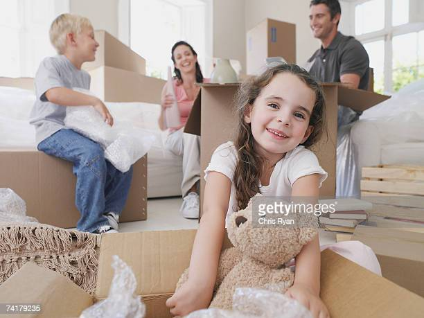 Girl with teddy bear in cardboard box with brother and parents in background