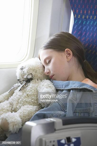Girl (6-8) with teddy bear sleeping on airplane