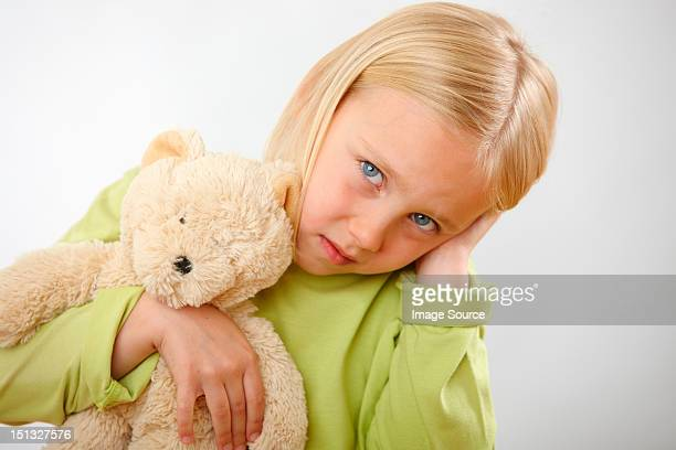 Girl with teddy covering ears