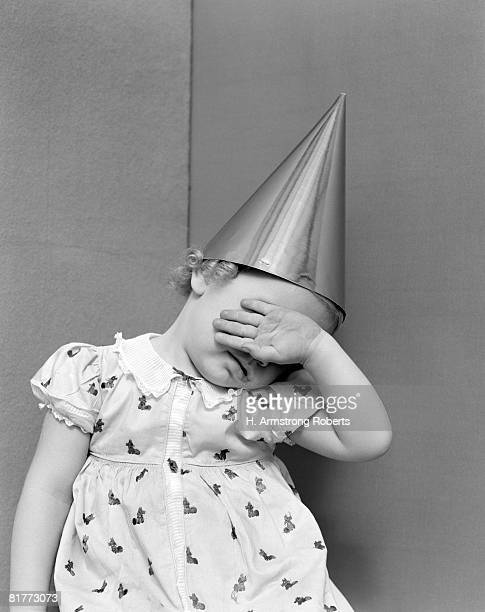 girl with the back of her hand covering her face sitting in a corner wearing a cotton print dress with white lace collar & dunce cap on her head. - dunce's hat stock pictures, royalty-free photos & images