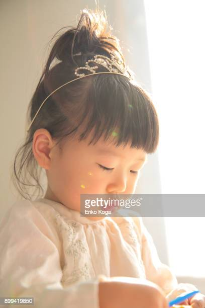 girl with tiara playing with toy - tiara stock pictures, royalty-free photos & images