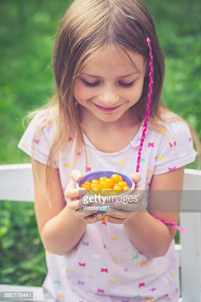 Girl with tomberries in bowl, yellow mini tomatoes