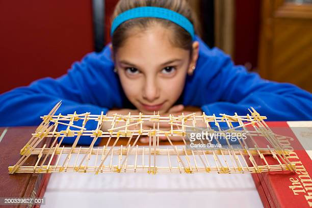 Girl (11-13) with toothpick bridge she built, portrait