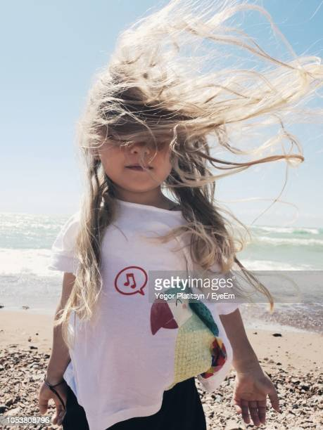 girl with tousled hair standing at beach - solo bambini foto e immagini stock