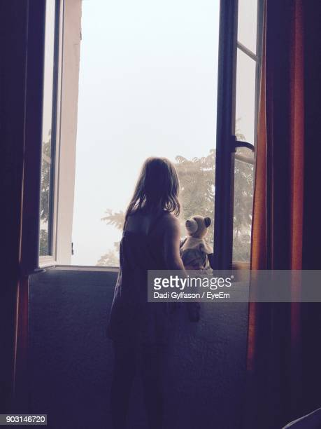 Girl With Toy Looking Through Window