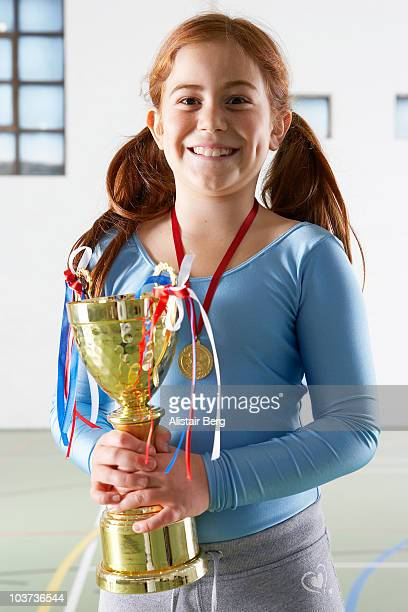 Girl with trophy in gymnasium