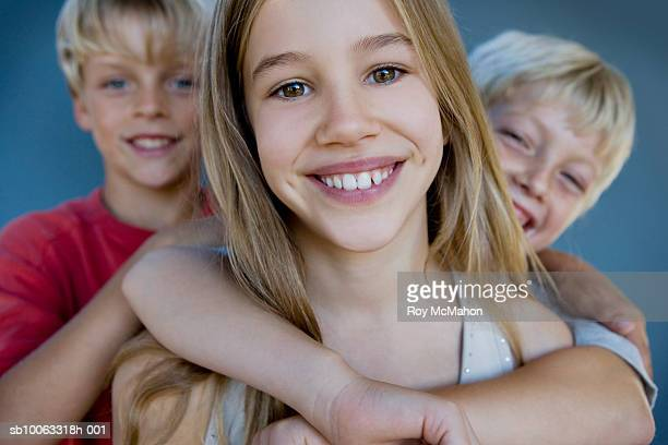 girl (10-11 years) with two boys (8-10 years), portrait, focus on foreground - 10 11 years stock pictures, royalty-free photos & images