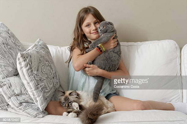 girl with two cats on sitting room sofa - two animals stock pictures, royalty-free photos & images