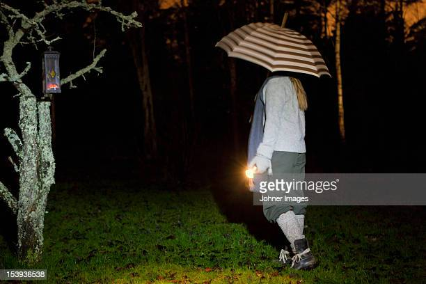 Girl with umbrella and torch walking in rain at night