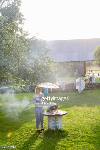 girl with umbrella having barbecue in garden - pluie humour photos et images de collection