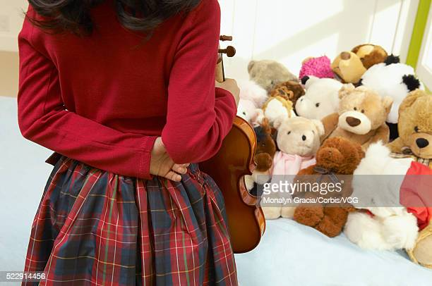 Girl with violin talking to her stuffed animals
