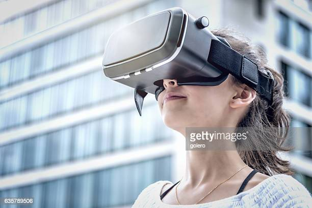 girl with virtual reality simulator in modern city