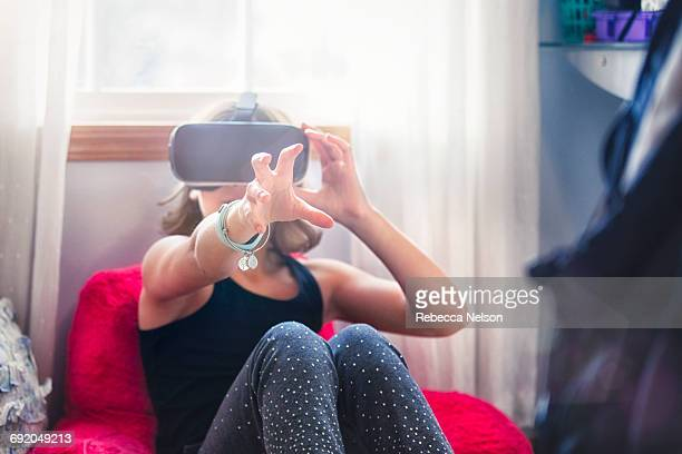 girl with VR headset reaching out towards camera