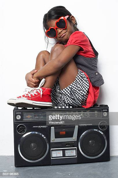 Girl with wearing red heart-shaped sunglasses sitting on ghetto blaster