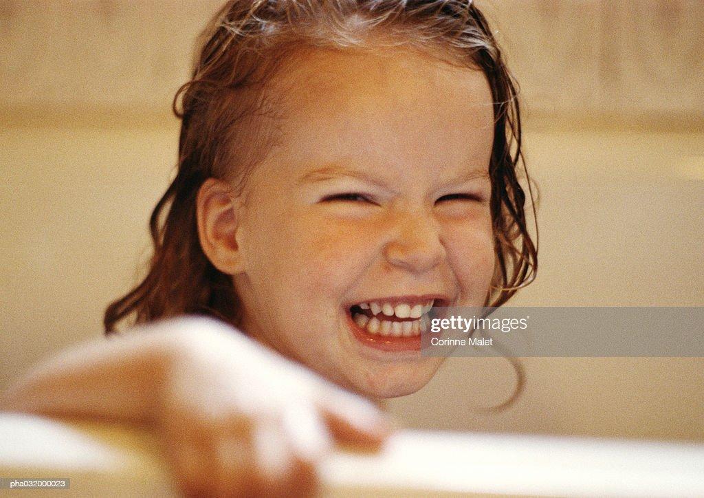 Girl with wet hair holding edge of bathtub, smiling : Stockfoto