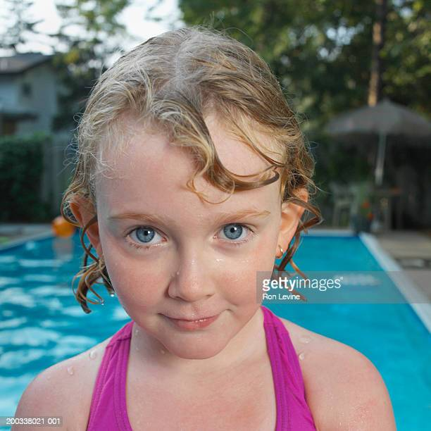 Girl (5-7) with wet hair in front of pool, close-up, portrait