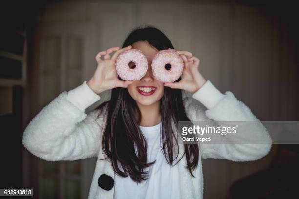 girl with white  donuts in front of her eyes