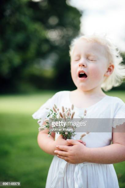 Girl with wildflowers sneezing
