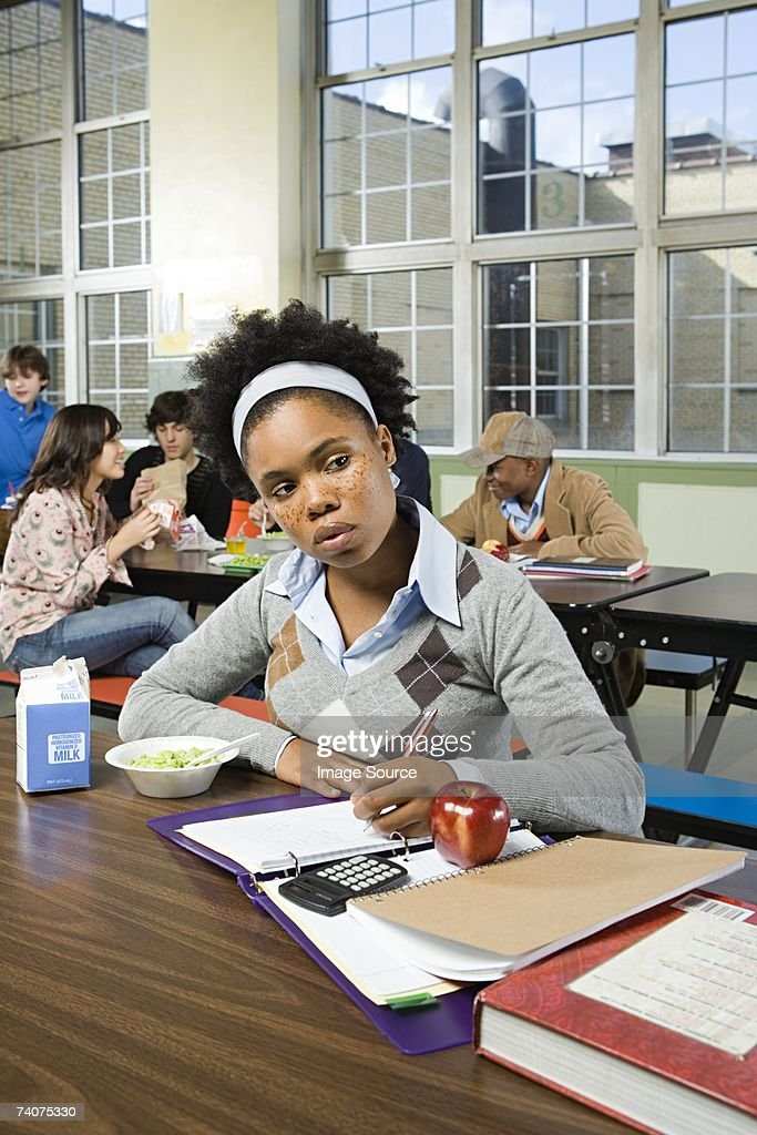 Girl working by herself in cafeteria : Stock Photo