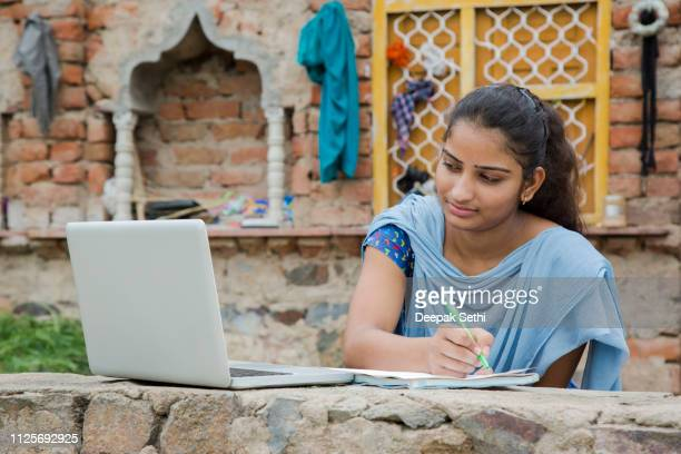 girl working on laptop - stock images, - village stock pictures, royalty-free photos & images