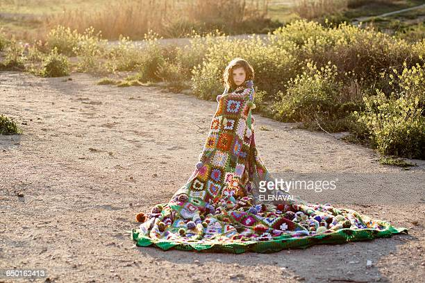 Girl wrapped in a blanket standing in a field