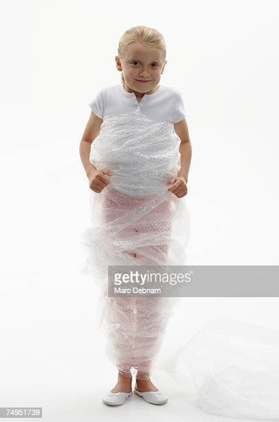Girl (7-9) wrapped in bubble wrap, smiling, portrait